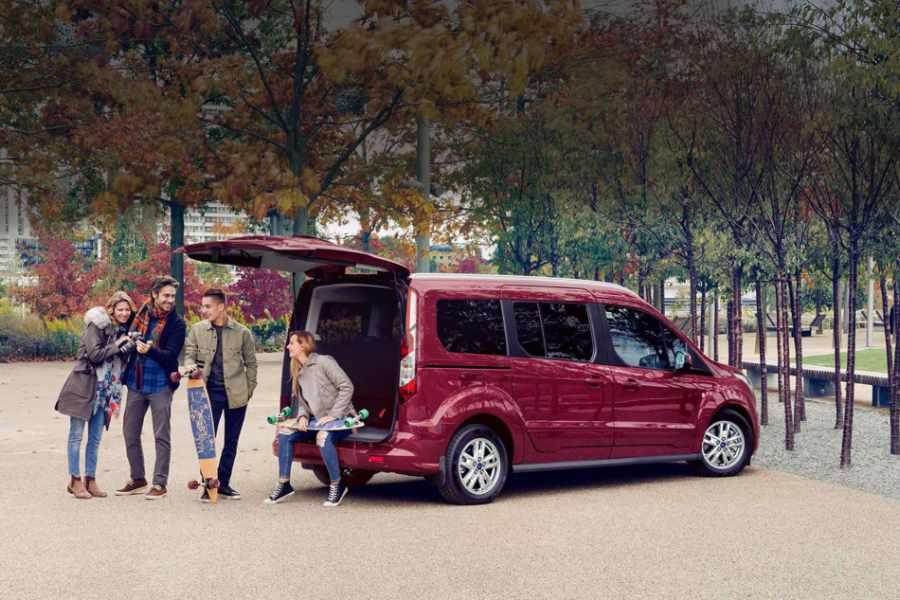 Roter Ford Tourneo Connect mit geöffnetem Kofferraum und Freunden