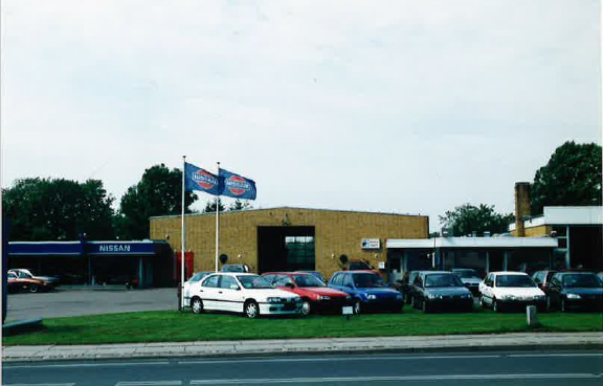 Lægsgaard i Bred, Bredgade 74. Pladeværksted helt til højre. Kontor ved glasvinduerne bag biler. Værksted i midten og til venstre udstilling. År 1999